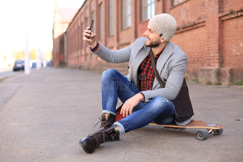 Handsome young man in grey coat and hat sitting on the longboard and taking selfie on the street in the city royalty free stock photo
