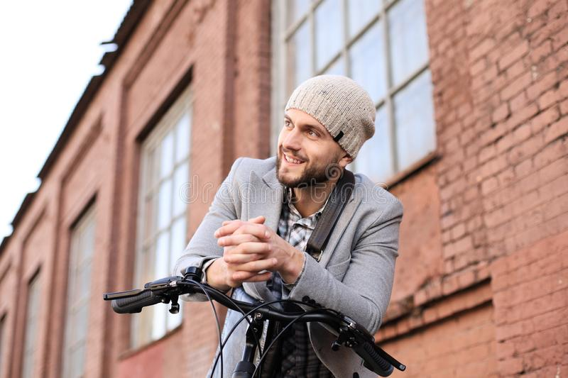 Handsome young man in grey coat and hat standing with his bicycle royalty free stock image