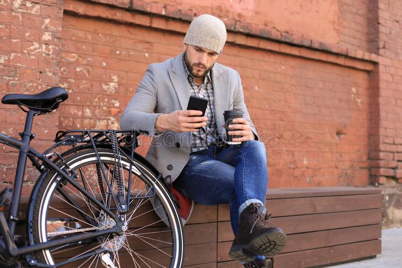 Handsome young man in grey coat and hat talking on the mobile phone and smiling while sitting near his bicycle outdoors.  royalty free stock images
