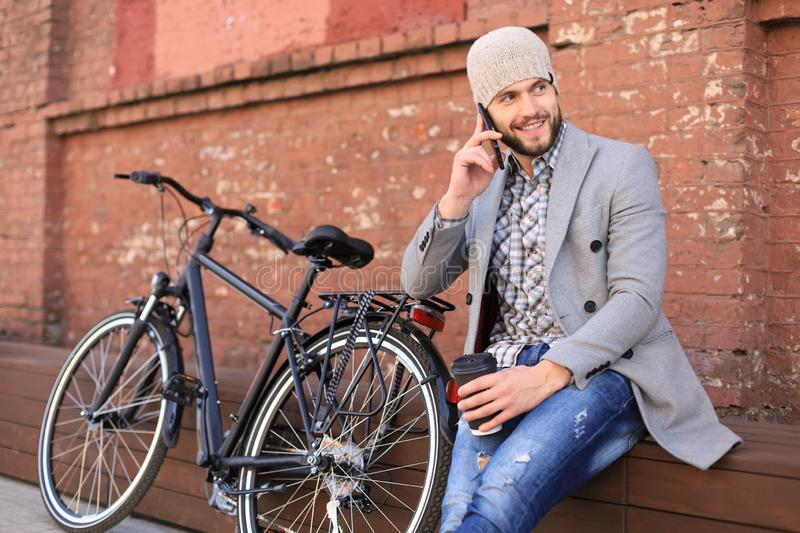Handsome young man in grey coat and hat talking on the mobile phone and smiling while sitting near his bicycle outdoors stock photo