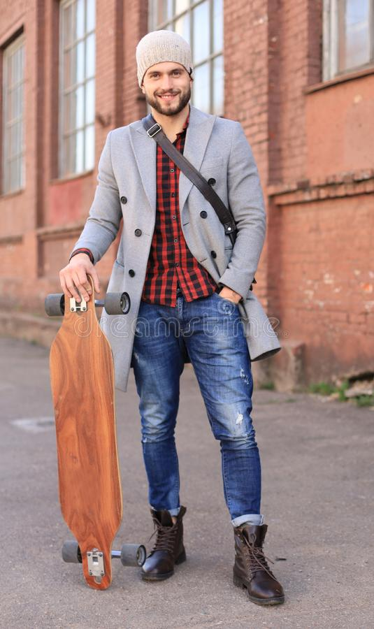 Handsome young man in grey coat and hat walking on the street, using longboard stock photography