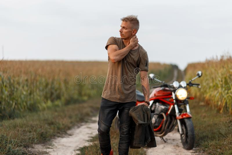 Handsome young man with a haircut in fashionable clothes with. A jacket near a motorcycle in a corn field. Concept travel stock photo