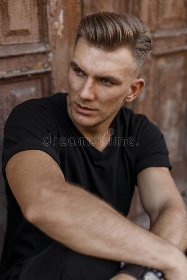 Handsome young man with hairstyle in black t-shirt royalty free stock images