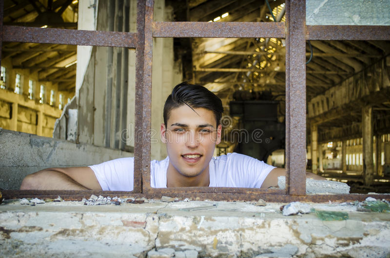 Handsome young man with happy expression in rusty stock photo