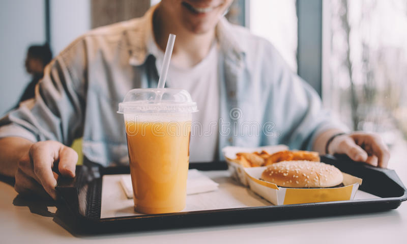 Handsome young man having lunch in cafe alone royalty free stock photo
