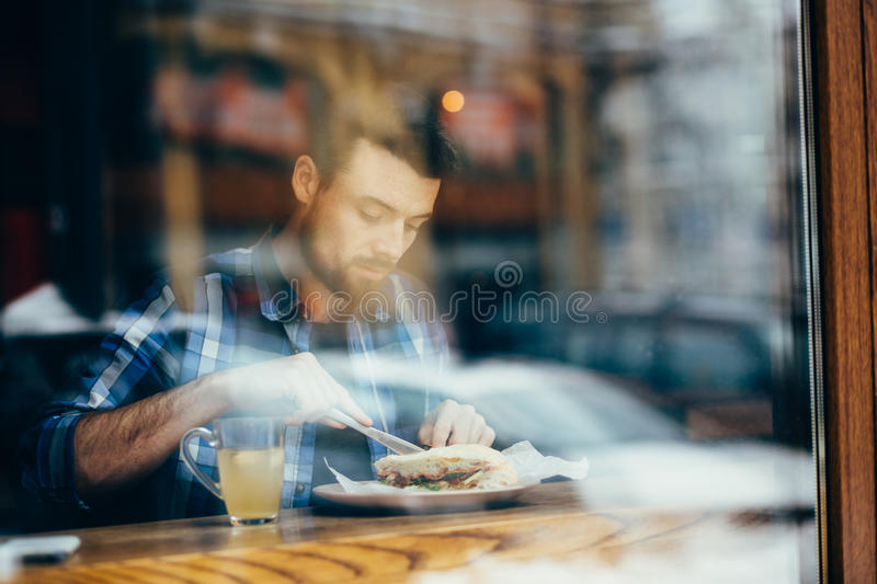 Handsome young man having lunch in elegant restaurant alone royalty free stock photos