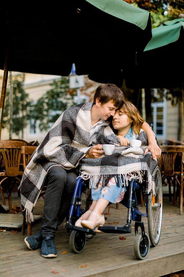 Handsome young man having some coffee and dating with pretty woman on a wheelchair on a sunny day. Man embracing woman royalty free stock photos