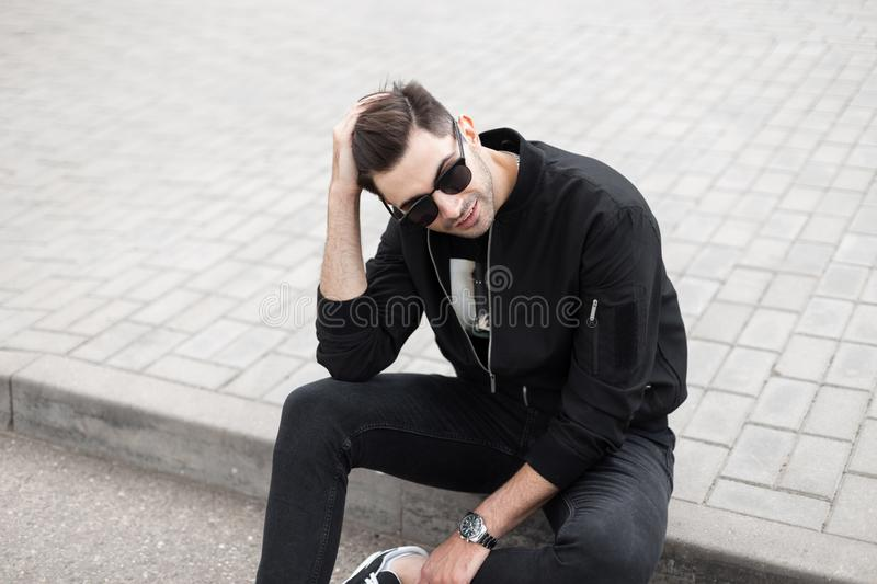 Handsome young man hipster with a trendy hairstyle in a fashionable black jacket in stylish sunglasses sits in a tile. And straightens hair. Urban guy in royalty free stock photography