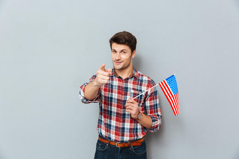Handsome young man hoding american flag and pointing on you. Over grey background royalty free stock photos