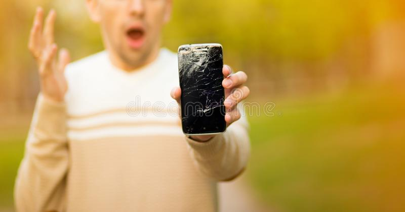 Young man hold broken smartphone screen stressed with hand on head, shocked with shame and surprise face, angry and frust stock images