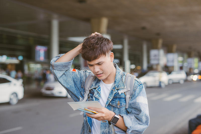 Handsome young man hold his head in hand and looking at his watche stock image