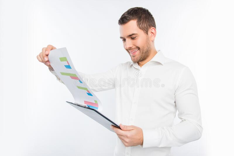 Handsome young man holding a folder and looking at the diagrama.  royalty free stock image