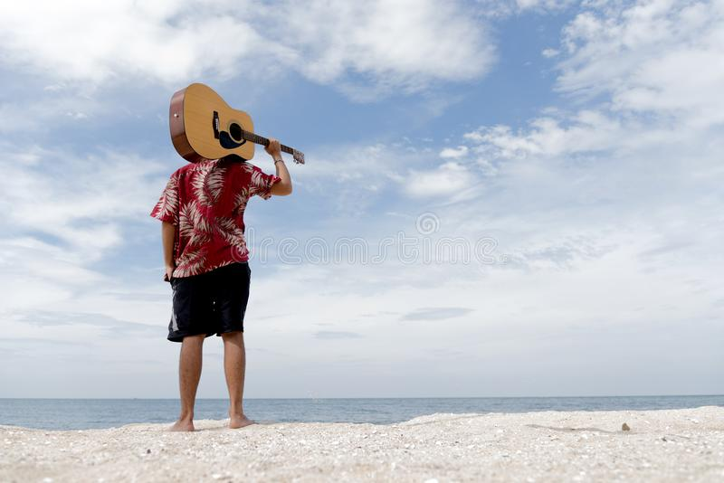 Handsome young man holding guitar over shoulder stock photography