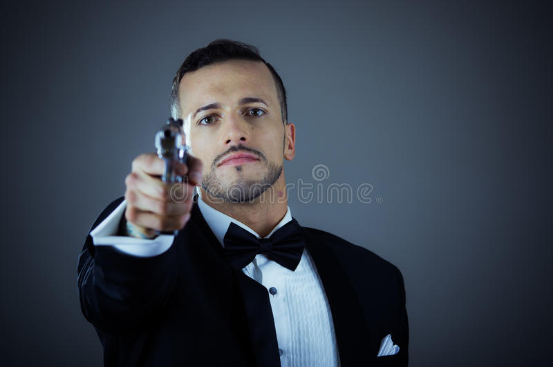 Handsome young man holding a gun royalty free stock image