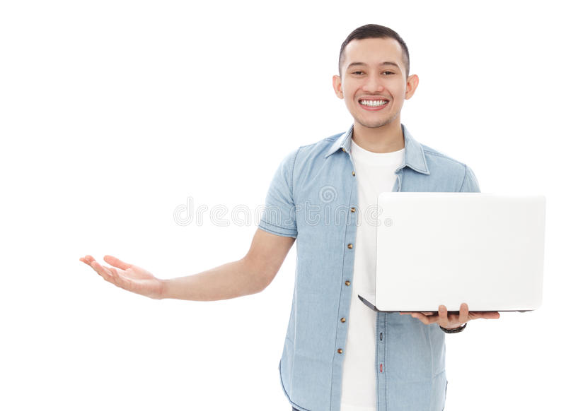 Handsome young man holding a laptop while presenting copy space stock images