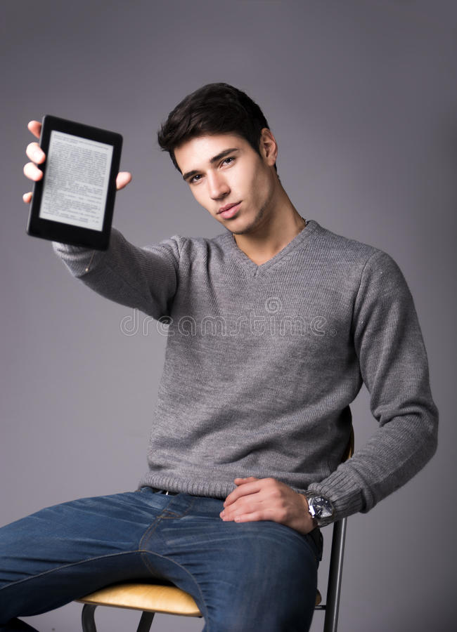 Handsome young man holding and showing ebook reader. And looking at camera, sitting on grey background stock images