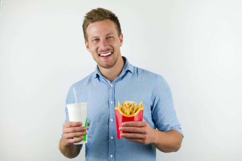 Handsome young man holds soda in papper cup and fries from fast food restaurant on isolated white background.  royalty free stock images