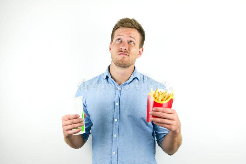 Handsome young man holds soda in papper cup and fries from fast food restaurant looks doubtful on isolated white. Background royalty free stock photos