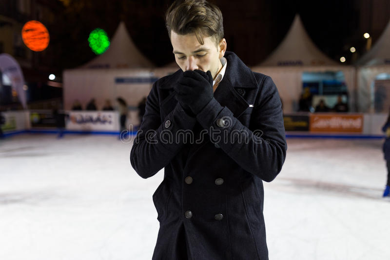 Handsome young man ice skating on rink outdoors. Portrait of handsome young man ice skating on rink outdoors royalty free stock images