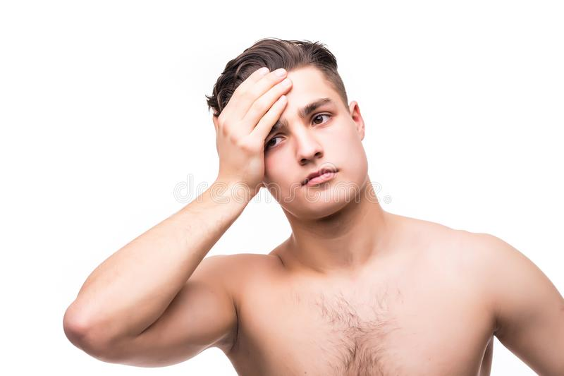 Handsome young man isolated. Portrait of shirtless muscular man is standing on white background. Man holding his temple. Experienc stock photography