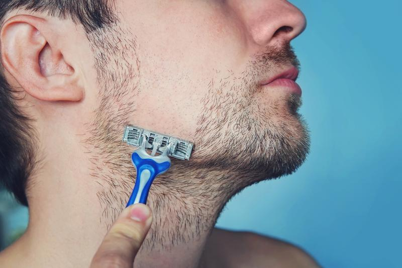 Handsome young man isolated. Portrait man is standing on black background with razor in hand while shaving. Men care concept. Get royalty free stock images