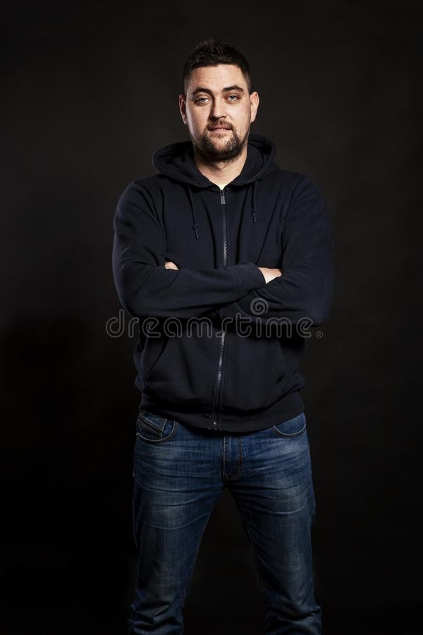 Handsome young man in jeans with a beard. Black background. stock photo