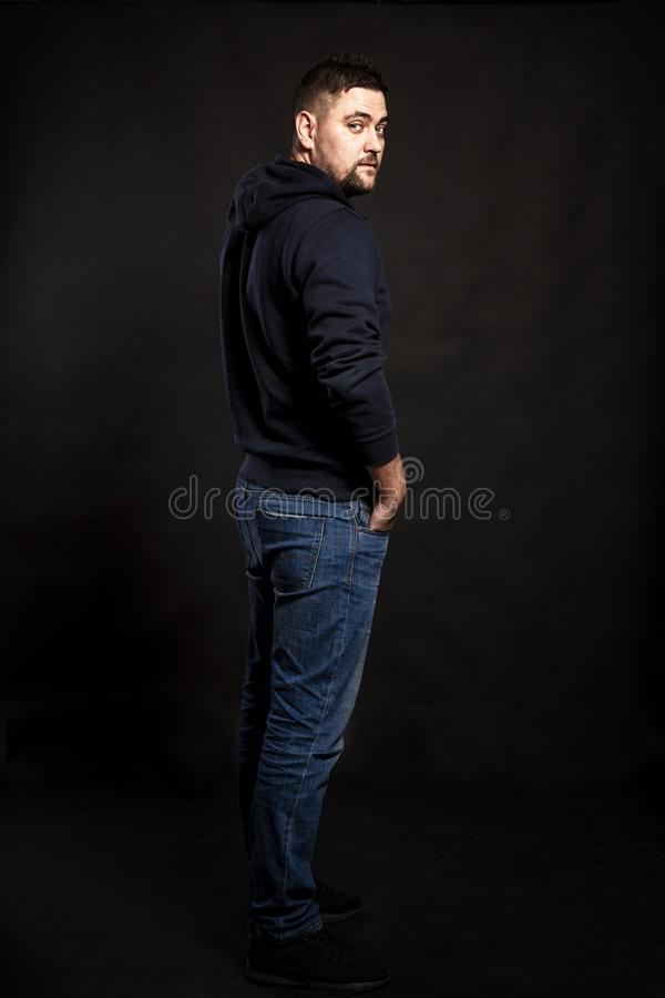 Handsome young man in jeans with a beard. Black background. stock photography