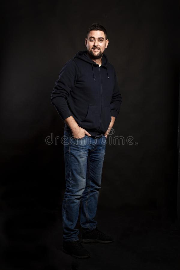 Handsome young man in jeans with a beard. Black background. stock images