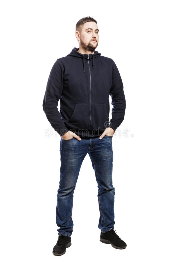 A handsome young man in jeans is standing. Hands in pockets. Isolated over white background. royalty free stock image