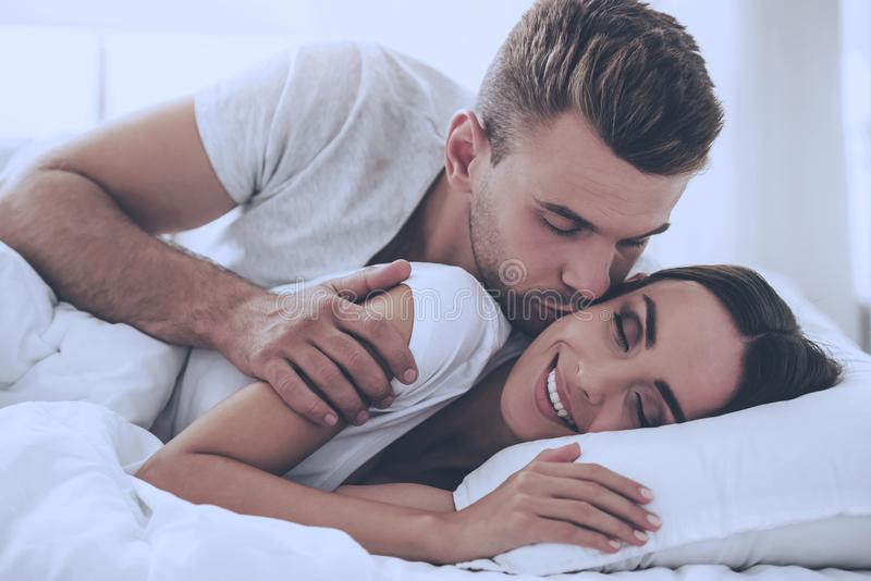 Handsome Young Man Kissing Beautiful Smiling Wife stock image