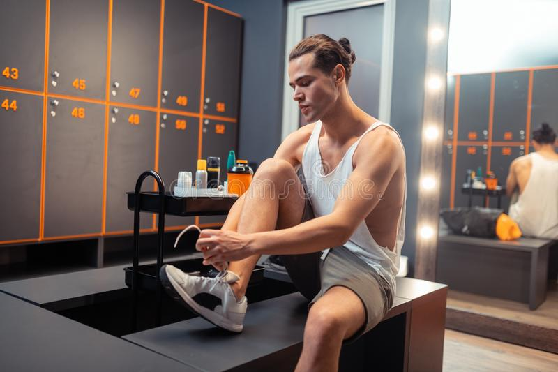 Handsome young man lacing his sports shoes royalty free stock photo