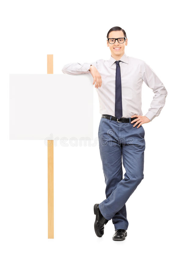 Handsome young man leaning on a blank poster. Full length portrait of a handsome young man leaning on a blank poster sign isolated on white background royalty free stock image