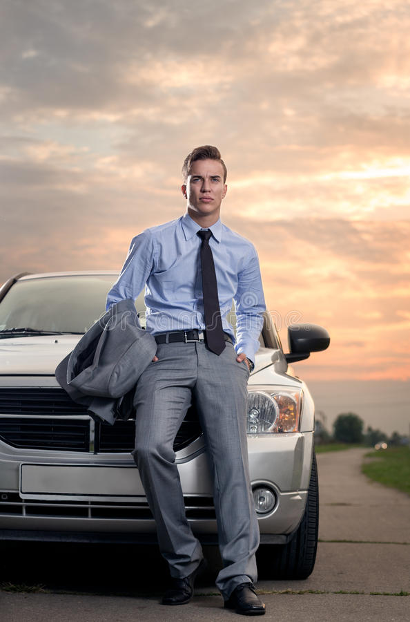 Handsome young man leaning on his car royalty free stock photo