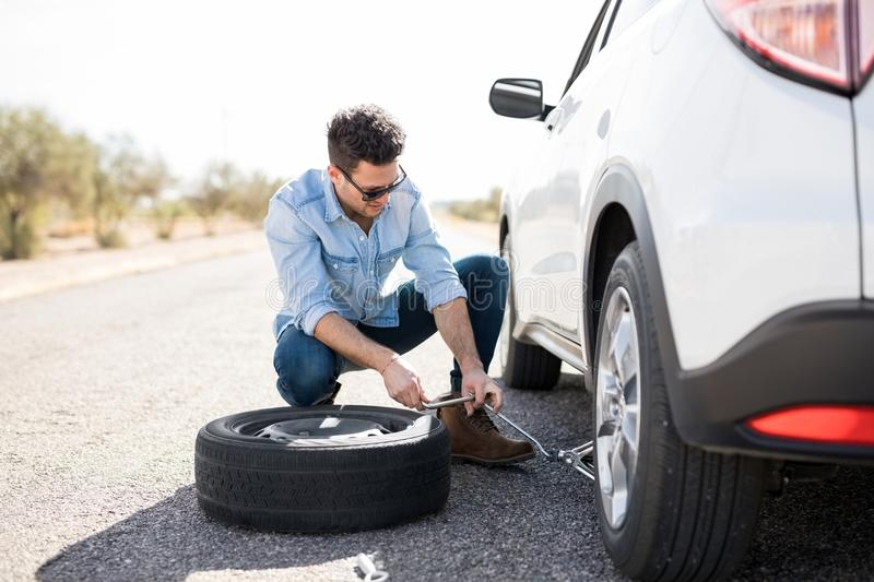 Man replacing the flat tire on the car. Handsome young man lifting the car on the jack for changing flat tire on the road royalty free stock photo