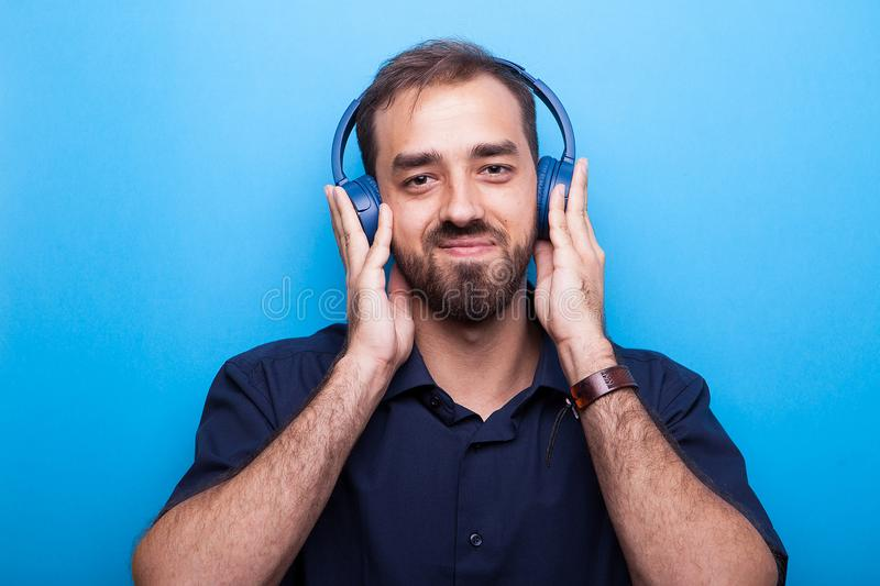 Handsome young man listening to music through headphones royalty free stock photo