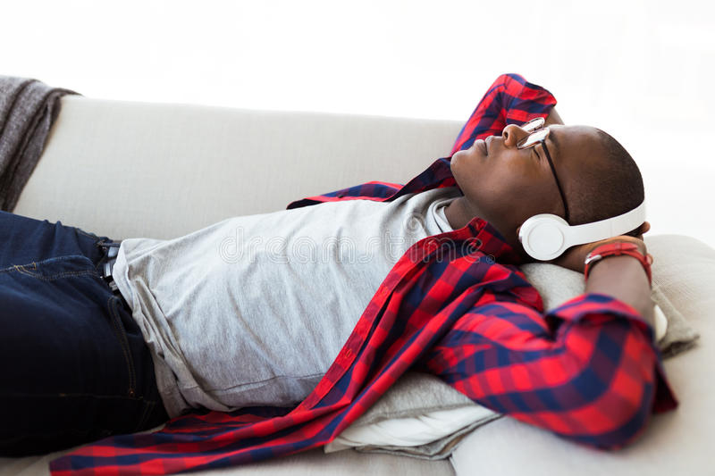 Handsome young man listening to music with headphones at home. stock image