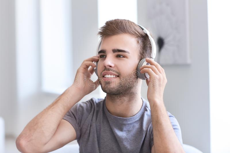 Handsome young man listening to music at home royalty free stock photography