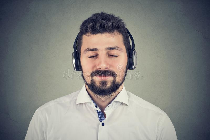 Handsome young man listening to music wearing headphones stock images