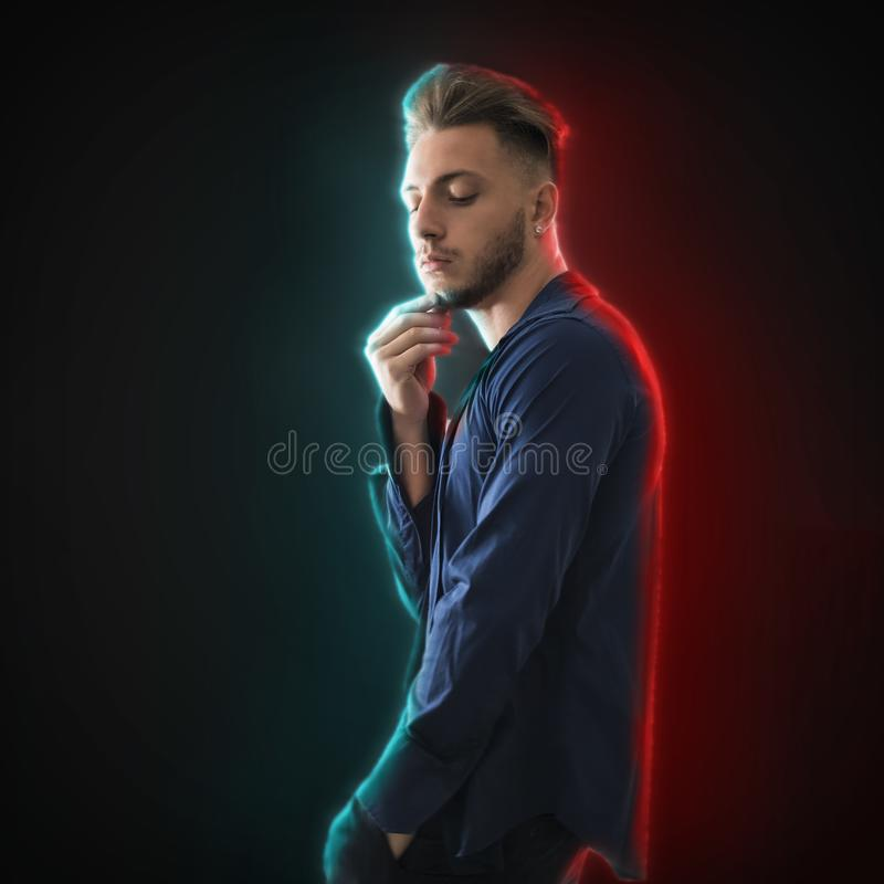 Handsome young man looking down to a side in studio shot stock images