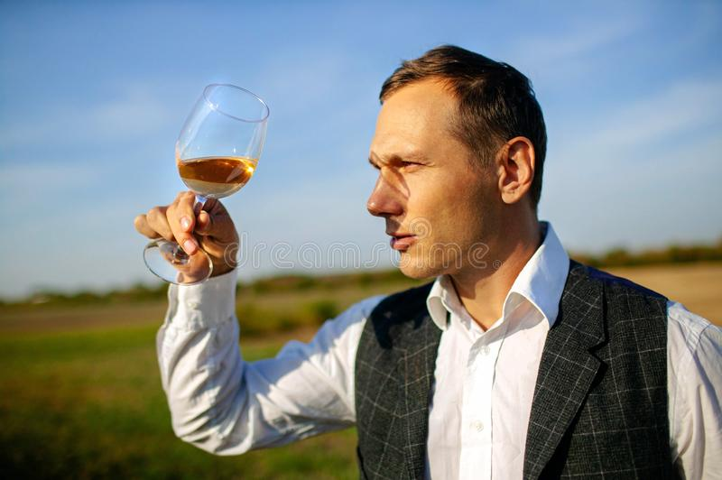 Handsome young man looking glass of wine before drinking in nature. royalty free stock photo