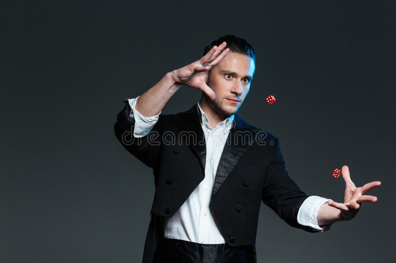 Handsome young man magician showing tricks with flying dice royalty free stock image