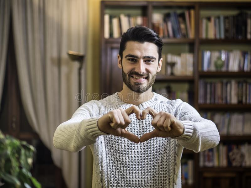 Handsome young man making heart sign with hands royalty free stock image