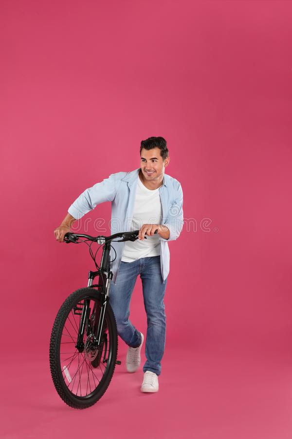 Handsome young man with modern bicycle stock photography