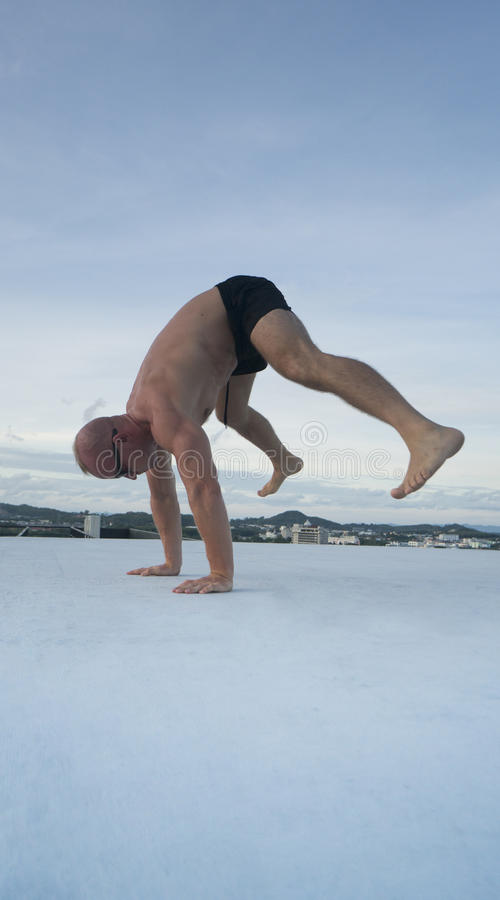 Handsome young man with naked torso doing brake dancing movements on a rooftop. Handsome young man with naked torso and sunglasses doing brake dancing movements stock images