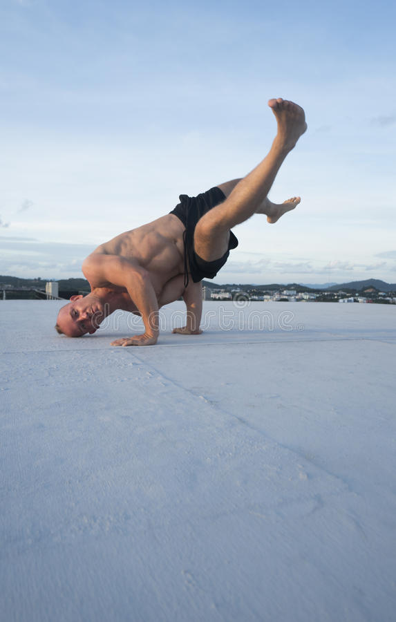 Handsome young man with naked torso doing brake dancing movements on a rooftop. Handsome young man with naked torso and sunglasses doing brake dancing movements stock image