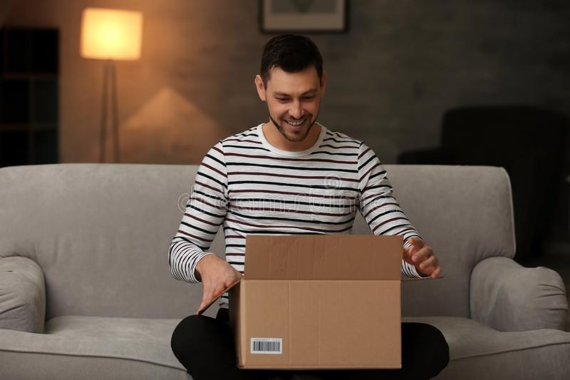 Handsome young man opening box with parcel stock image