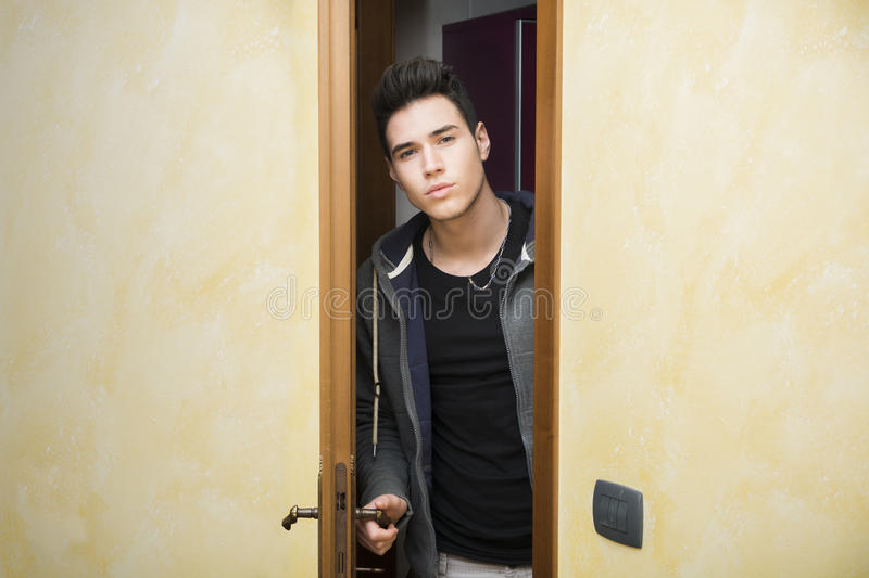 Handsome young man opening door to enter stock images