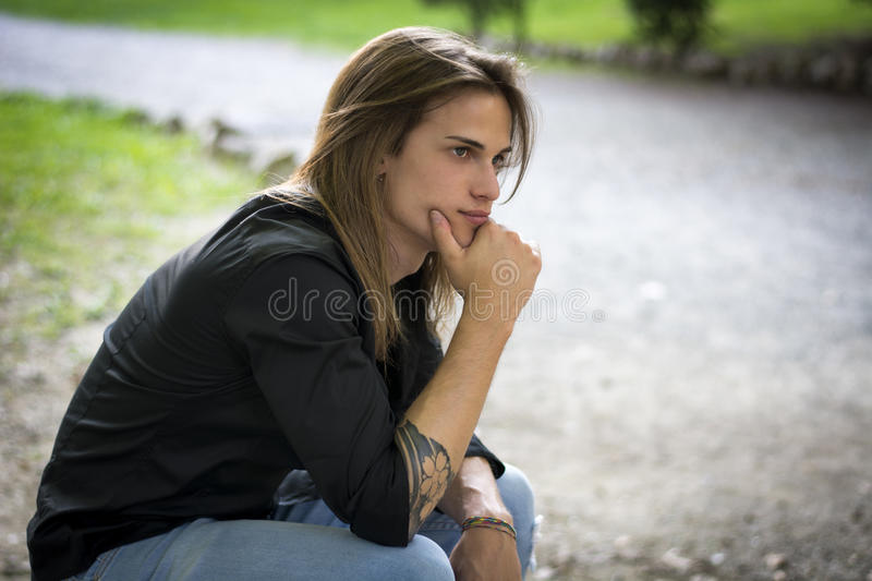 Handsome young man outdoor thinking, sad or worried royalty free stock photography