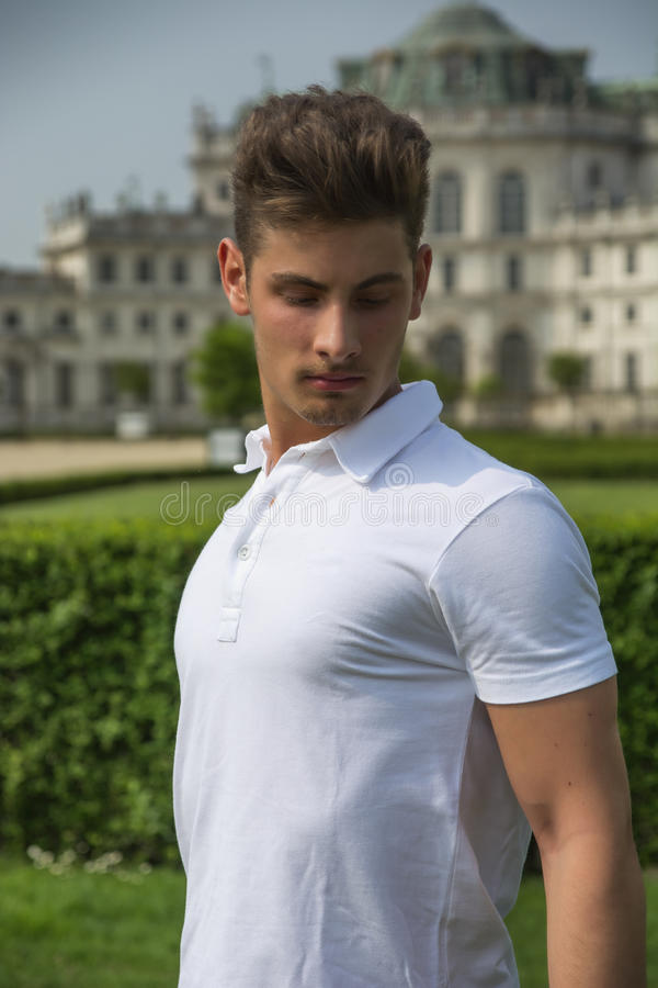 Handsome young man outdoors, old elegant royal palace behind him royalty free stock photos