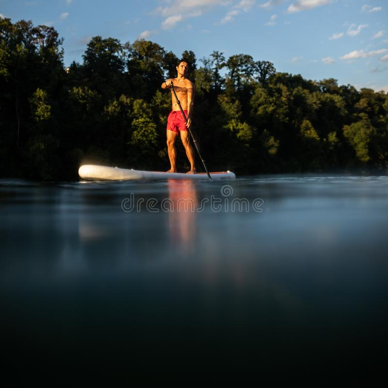 Handsome young man on a paddle board stock image
